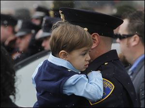 A police officer holds a young child at the funeral for Officer Andrew Dunn.