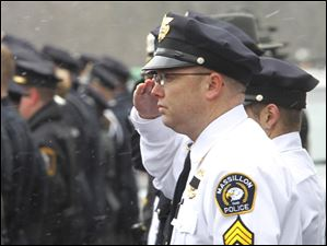 A police officer from Massillon, Ohio, salutes at Officer Andrew Dunn's funeral.