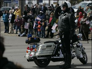 A motorcycle police officer salutes the Andrew Dunn procession on its way to the Calvary Cemetery  Mausoleum in Sandusky, Ohio.