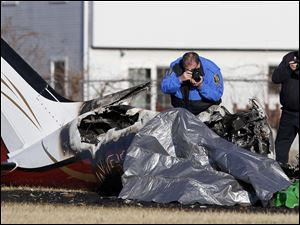 The wreckage of the aircraft, partially covered by tarp, is photographed by investigators.