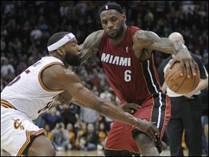 Cleveland Cavaliers' Baron Davis, left, defends Miami Heat's LeBron James (6) in the fourth quarter. The Cavaliers won 102-90.