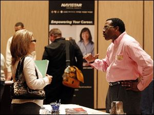 Kerry Murray, right, of DeVry University talks with a job seeker at a March job fair in Indianapolis.