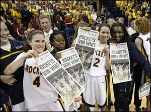Toledo's Naama Shafir, left, and other teammates hold The Blade announcing their victory over USC to win the WNIT championship.
