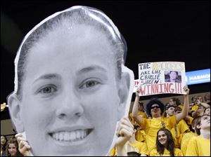 A Toledo fan holds a giant blow-up poster of Rockets player Naama Shafir's face.