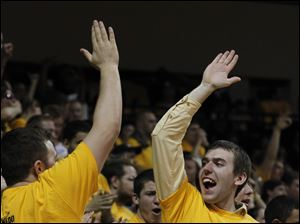 Toledo student John Gaspar, right, high-fives a fellow UT student after the Rockets score against USC.