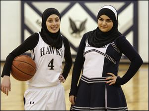 Yasmin Abdelkarim, 17, left, and Amal Mohamed, 15, right, are Muslim students at Maumee Valley Country Day School, dressed here in the attire they wear when they participate in their respective athletic activities. Yasmin plays basketball and Amal is a cheerleader.