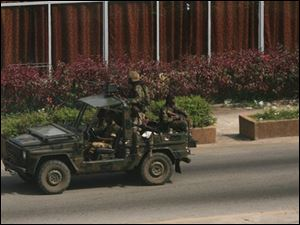 Soldiers loyal to Laurent Gbagbo patrol a street in the central Plateau neighborhood of Abidjan, Ivory Coast, Saturday.
