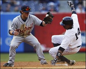 Detroit second baseman Will Rhymes attempts to tag out New York's Curtis Granderson (14) as he steals second base.