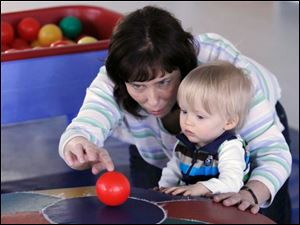Speech and language specialist Heidi Crawford works with Isaiah Lake, 15 months.