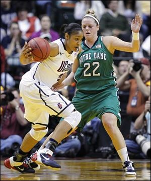 Connecticut's Maya Moore, left, drives on Notre Dame's Brittany Mallory (22).