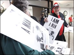 Cindy Weible, with OAPSE, passes out a sign to Toledo firefighter Rich Duffey at the UAW Local 14 hall during a