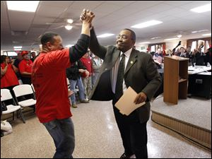 Ray Wood, president of UAW Local 14, left, clasps hands with Pastor Kevin Bedford, president of the NAACP, after Bedford spoke at the UAW Local 14 hall during a