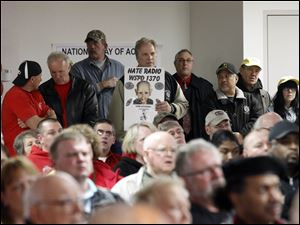 Paul Wohlfarth, with UAW Local 12, holds a sign at the back of a standing-room only rally at the UAW Local 14.