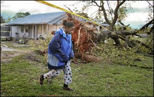 Marcie Moore walks Tuesday near a downed tree in Jackson, Ga. Her 4-year-old son, Alix Bonhomme III, was killed along with his father Alix Bonhomme Jr. in the severe storm that whipped across the South.