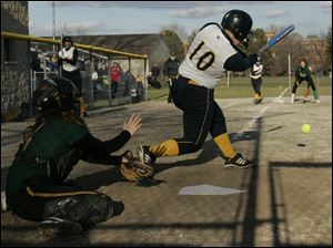 Notre Dame's Bitty Treece (10) makes a key hit during game against Clay. Abbey Herrera is Clay's catcher.
