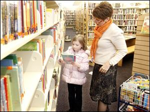 At the Waterville branch of the Toledo-Lucas County Public Library, Karen Wiggins helps Alivia Taylor, 7, of Monclova Township find materials. The library has far more to choose from today than at its start.