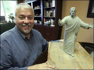 "Ron Carter, church administrator for Solid Rock Church in Monroe, Ohio, displays the model of the new statue ""Come Unto Me"" that will replace the former ""King of Kings"" statue, which was struck by lightning and burned."