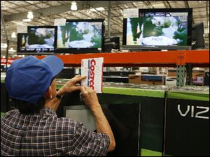 A shopper notes television prices at the Costco Wholesale store in Glendale, Calif.