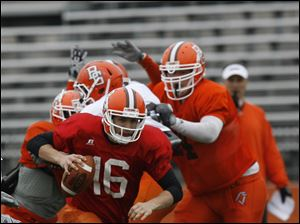 Quarterback Trent Hurley (16) scrambles during the scrimmage.