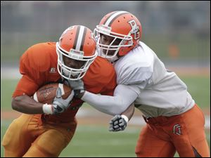 Tyler Williamson (28) is tackled by Jovan Leacock (11).