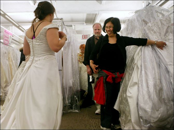Filene's Basement Wedding Dress Mary Fitzgerald, from New Brunswick, N.J., shows a bridal gown to her parents Pat, center, and Sue Fitzgerald, from Utica, N.Y., during the