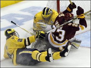 Minnesota Duluth right wing J.T. Brown (23) collides with Michigan goalie Shawn Hunwick, center, after a holding penalty by Michigan defenseman Jon Merrill, left, during the third period.