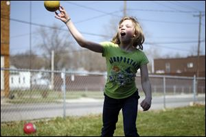 Hailie Draper, 10, takes aim in an attempt to hit her brother with a ball during a game of dodge ball in the front yard of their home on Western Avenue. The high temperature Sunday topped out at 83 degrees and tied the record.