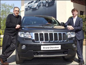 Fiat and Chrysler CEO Sergio Marchionne, left, poses with the new Grand Cherokee Jeep and Mike Manley, Jeep brand CEO, during a presentation Monday in Balocco, near Turin, Northern Italy.