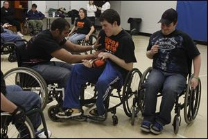 Amit Goyao, left, of Toledo, tries to 'tackle' Nick Hyndman, right, a member of the Toledo Crash wheelchair football team from Perrysburg, during a scrimmage with the University of Toledo Rec Therapy Club.