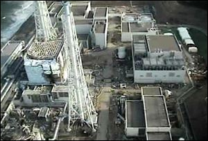 An aerial view shows the damaged reactor building of Unit 4, left, of the tsunami-crippled Fukushima Dai-ichi nuclear power plant in Okuma town, Fukushima Prefecture, northeastern Japan, in this image taken Sunday by T-Hawk drone aircraft and released by Tokyo Electric Power Co.
