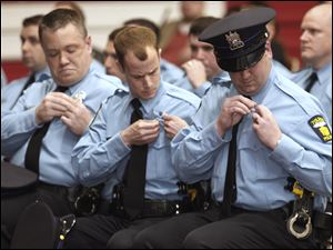 Anthony Foley, left, Melvin Haney, Jr., center, and Brian Heath pin on their badges after being sworn in as members of the Toledo Police Department Tuesday night.