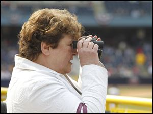 Liz Geha of Sylvania, takes in the action during the Mud Hens home opener at Fifth Third Field. She said the players look great in baseball uniforms.