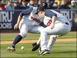 Mud Hens third baseman Danny Worth, left, and pitcher Matt Hoffman, right, converge on a bunt by Clippers player Ezequiel Carrera.