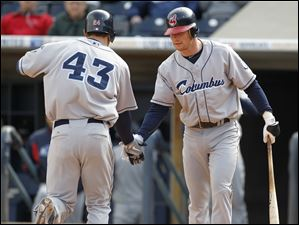Cleveland Indians player Grady Sizemore (43), on a rehab assignment with the Columbus Clippers, is congratulated by teammate Jason Donald after Sizemore hit a home run during the third inning of the Mud Hens home opener.