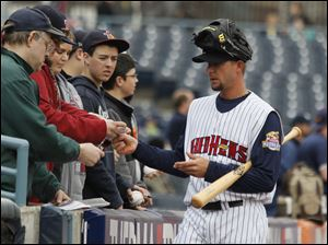 Mud Hens player Clete Thomas wears his glove on his head as he signs autographs for fans.