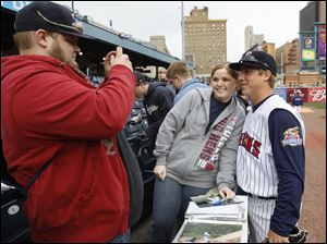 George Clark, left, photographs his sister Jessica Clark, of Chelsea, Michigan, posing with Toledo Mud Hens player Andy Dirks.