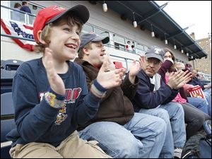 Isaac Monnin, 8, along with his father Randy Monnin, of Sylvania, Rick Monnin, Randy's brother, of Sylvania Township, and his daughter Kristy Monnin, 12, cheer at the Mud Hens players are introduced during the Mud Hens home opener at Fifth Third Field.