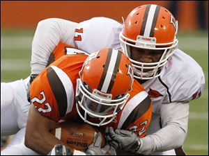 Bowling Green Orange Squad running back Erique Geiger (22) is brought down by White Squad defender Jovan Leacock (11).