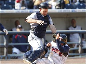 Mud Hens shortstop Cale Iorg is caught stealing home as Columbus Clippers catcher Luke Carlin applies the tag.