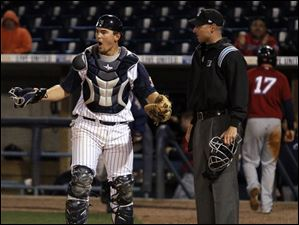 Toledo catcher John Murrian (23) protests home plate umpire Derek Crabill's call that Columbus Clipper DH Jordan Brown (35) was safe at the plate.