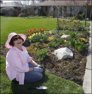 Toledoan Donna Coleman McCarty, who dug into her hobby in earnest 40 years ago, tends to her Shoreland Avenue garden.
