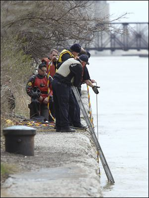 Toledo firefighters tend to a diver in the water while another sits ready as they search the Maumee River for evidence just downstream from the Willis B. Boyer Museum Ship in East Toledo. Divers found nothing and will resume the search, but not Saturday because of high winds in the forecast, Fire Chief Mike Wolever said.