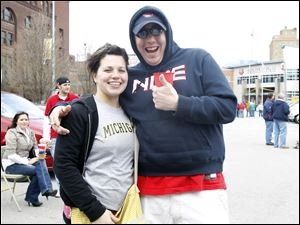 Katie Lohman, left, and Jim Paul, right, enjoy a pre-game tailgate before the Mud Hens' home opener.