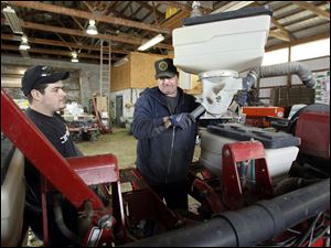 Bill Myers, right, and his son John Myers work on their corn planter in Oregon, Ohio. Mr. Myers says he'll increas corn production by 15 percent to 20 percent because he cut back last year.