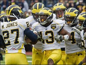 Michigan safety Carvin Johnson (13) celebrates his interception with Mike Jones (27), Cameron Gordon (4), and Marrell Evans, far right. Johnson also had seven tackles.
