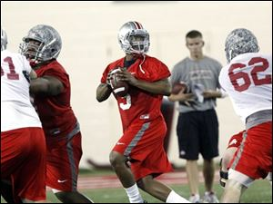 Ohio State quarterback Braxton Miller (5) drops back to pass during a practice earlier this spring in Columbus.