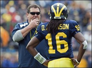 New Michigan coach Brady Hoke discusses an incomplete pass with returning quarterback Denard Robinson at Michigan Stadium