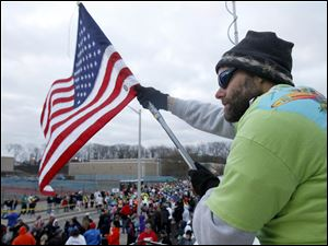 David Black waves an American flag during the National Anthem prior to the start of the Glass City Marathon.