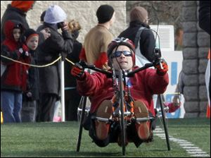 Richard Biggins ofToledo crosses the finish line as the first wheel chair in from the race during the Glass City Marathon.