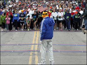 Tom Falvey, center, holds the U.S. flag before the crowd of runners set to take off.